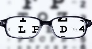 eyeglasses in front of an eye chart